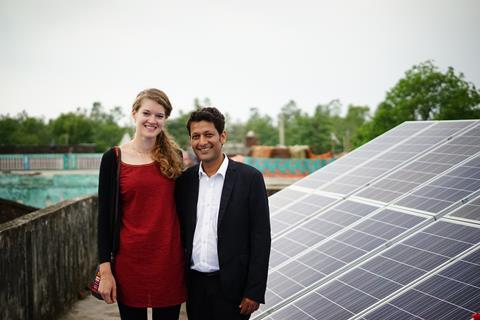 Image showing Amit and Clem in India, with solar panels in the background